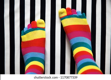 Two feet in colored striped socks on the black and white striped floor