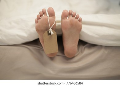 Two feet of dead body, with identification tag - blank sign attached to a toe. Covered with a white sheet.