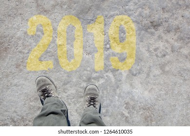 two feet in grey boots and the word 2019 written on the ground, business concept for turn of the year, new start and beginning
