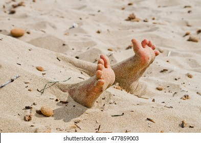 two feet on the beach in rigor mortis protrude from the sand