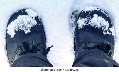 Two feet in shoes standing in snow