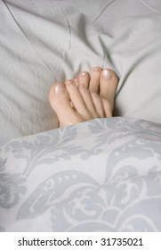 Two feet snuggled in a duvet for warmth,  shot landscape
