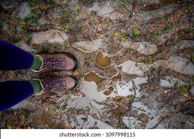 Two feet standing on a muddy, wet path, in. hiking boots