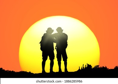 Two fellow stand on the mountain top and and look at the sunset. Traveler silhouettes. Rear view against the backdrop of a giant sun disk