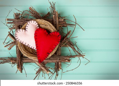 Two felt hearts in a rustic wooden nest on a retro turquoise background