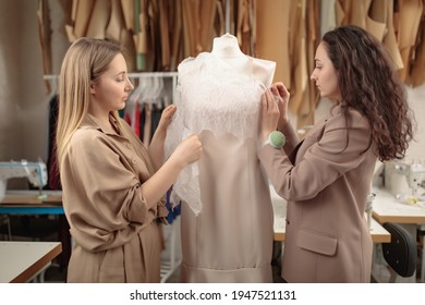 two femail Dressmakers or tailors or fashiondesigners or seamstresses picking a tailor dummy mannequin in a lace cloth at own workshop studio. Small handmade business concept