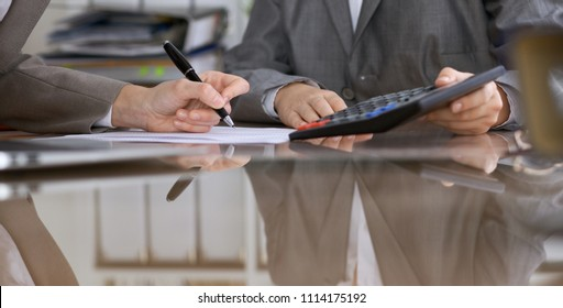 Two female accountants checking financial statement or counting by calculator income for tax form, hands close-up. Internal Revenue Service inspector checking financial document. Planning budget and