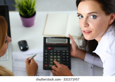 Two female accountants counting on calculator income for tax form completion closeup. Internal Revenue Service inspector checking financial document. Planning budget, audit, insurance concept