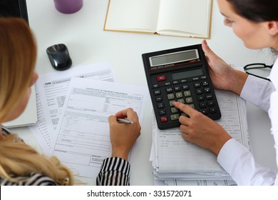 Two female accountants counting on calculator income for tax form completion hands closeup. Internal Revenue Service inspector checking financial document. Planning budget, audit, insurance concept