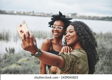 Two female afro american friends have a walk around beach. Taking selfie.