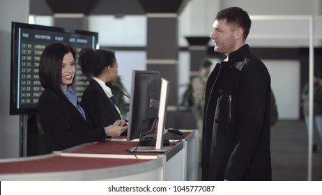 Two female airport security personnel checking identification at a check-in or boarding counter at the departure terminal holding the passports of two male passengers