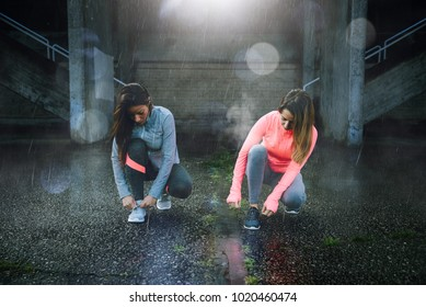 Two female athletes lacing shoes and getting ready for urban running workout under cold raining weather. Winter training and fitness motivation concept.