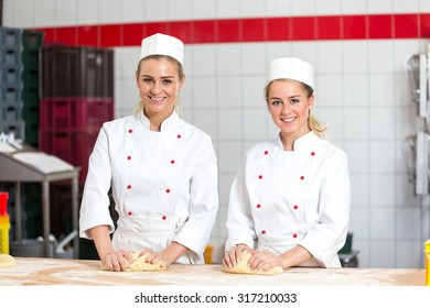 Two female bakers in a bakery kneading dough at bakery