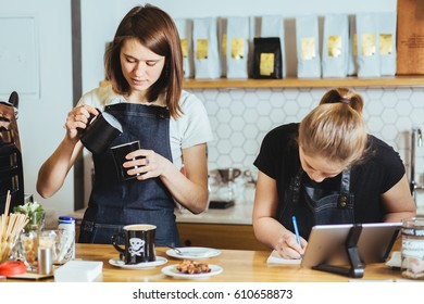 Two female baristas working behind counter at the coffee shop