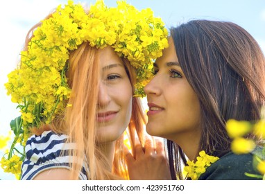 two female best friend in a field with yellow flowers of rapeseed having fun