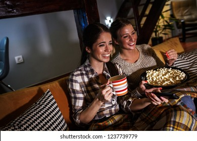 Two female best friends sitting at home on pleasant evening and watching a television show.