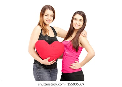 Two female best friends standing close together and holding a red heart isolated on white background