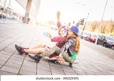 Two female best friends taking selfie outdoors - Cheerful girlfriends having fun