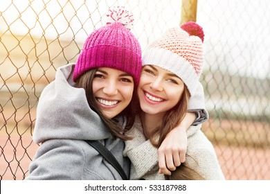 Two female besties in knit beanies and coats hugging and smiling. Two young best friends enjoying outdoors, loving and hugging each other. Vibrant color, natural light, medium retouch.