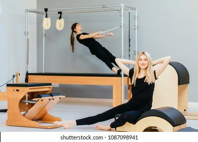 Two female in black sportswear working out on spine corrector and cadillac - modern pilates equipment in gym. Health and rehabilitation concept.