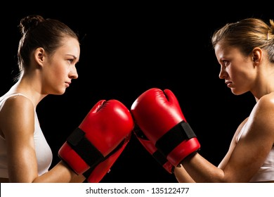 two female boxers face each other, pushing the boxing gloves, start a fight