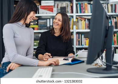 Two female business partners or colleagues sitting working together over paperwork looking at each other smiling and laughing