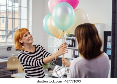 Two female business partners or colleagues holding a bunch of multicolored party balloons with a happy smile in the office as they celebrate their success or anniversary