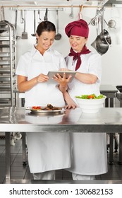 Two female chefs looking for recipe on a digital tablet while cooking at kitchen