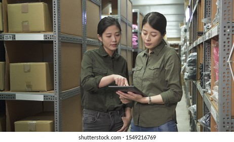 two female colleague workers checking results on digital tablet in large stockroom. lady employee coworkers wearing uniform and discussing on mobile pad in warehouse. asian women teamwork partners