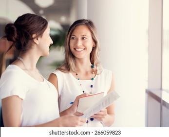 Deux collégiennes debout l'une à côté de l'autre dans un bureau