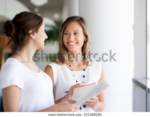Zwei weibliche Kollegen stehen nebeneinander in einem Büro