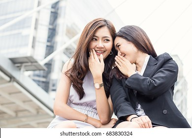 Two female co-workers whispering outside the office (gossip, office, women)