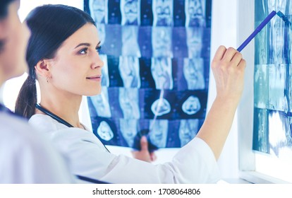 Two female doctors pointing at x-rays in a hospital