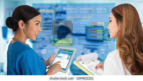 Two female doctors work together by one working with electronic medical records on digital tablet and another working on paper documents.