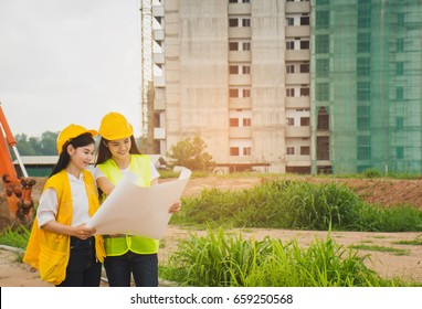 Two female engineers are reading a blueprint for a new building project.
