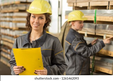 Two female engineers standing and checking material in storehouse. Women wearing yellow helmets and grey uniform, pointing at pallet and keeping documents. Professionals on industry object.