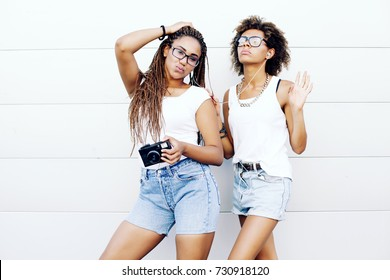 Two Female Friends Bonding Outdoors. Two young beautiful afro girls are walking through the city and listen to music. lifestyle