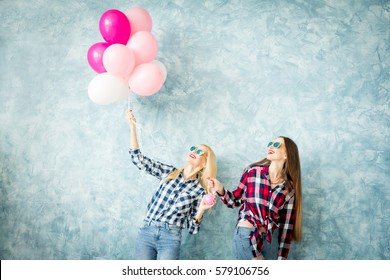 Two female friends in checkered shirts having fun with air balloons on the blue wall background