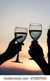 Two female friends clinking wine glasses close to the sea during the sunset. Summer lifestyle concept. Glasses of wine in the hands of women.