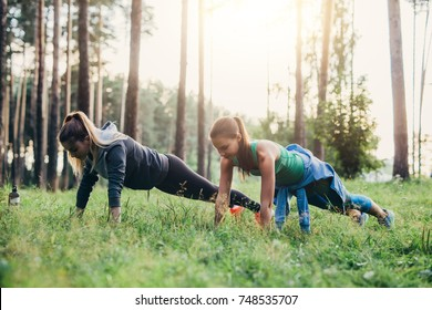 Two female friends doing push-up exercise training outdoors in forest