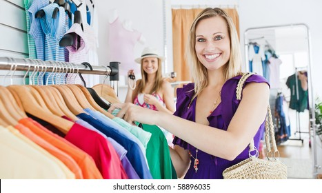Two female friends doing shopping together in a clothes store