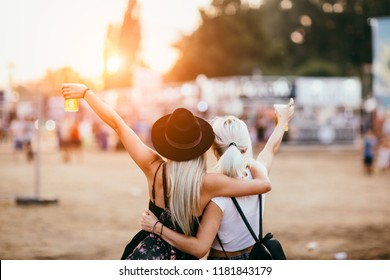Two female friends drinking beer and having fun at music festival. Back view
