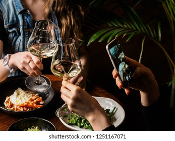 Two female friends eating helthy food in restaurant and clinking glasses with wine