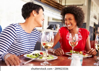 Two female friends eating at a restaurant