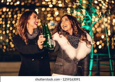Two female friends enjoy the night out, looking each other and laughing with bottles of beer in their hands.