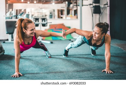 Two female friends exercising together in the gym
