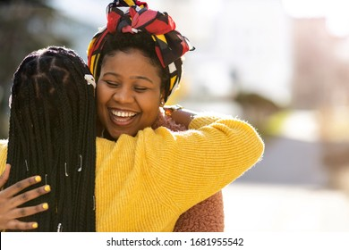 Two female friends greeting each other and embracing