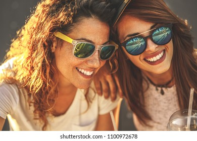 Two female friends hangout at the city street.Laughing and fun.Close up portrait.