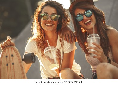 Two female friends hangout at the city street.Laughing and fun.Drinking juice.