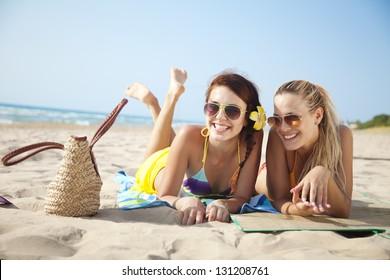 zwei Freundinnen, die sich am Strand amüsieren